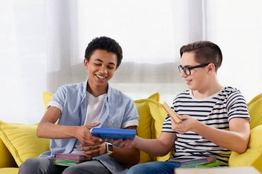 caucasian teen boy passing books to african american friend at home