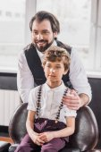 Fotografie adorable little kid sitting on chair at barbershop while happy barber standing behind him
