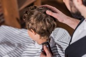 Fotografie high angle view of barber cutting hair of little kid with Hair Clipper