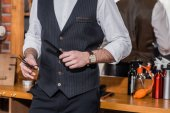 Fotografie cropped shot of stylish barber with scissors and comb
