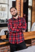 handsome young barber in plaid shirt leaning back on workplace in barbershop
