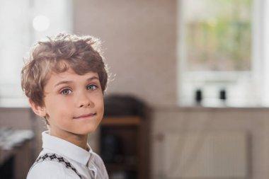 smiling little kid looking at camera at barbershop