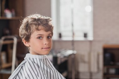 adorable little kid covered with striped cloth at barbershop