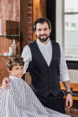Handsome bearded barber with little kid covered with striped cloth looking at camera in barbershop stock vector
