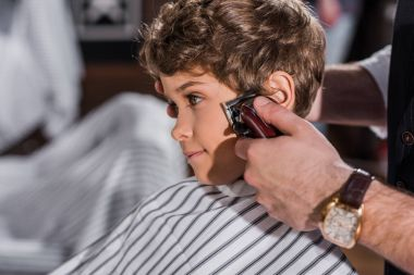 adorable curly kid getting haircut with Hair Clipper