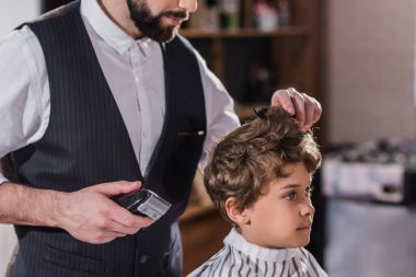 Cropped shot of barber cutting hair of little kid with Hair Clipper stock vector