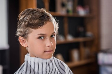 close-up shot of adorable little kid covered with striped cloth at barbershop