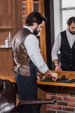 handsome young barber in stylish vest taking tools from rubber mat on workplace