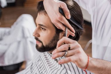 cropped shot of barber cutting hair of customer with scissors