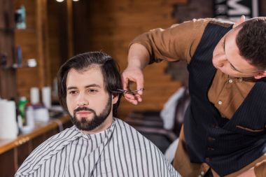 Handsome young man getting haircut from professional barber at barbershop stock vector