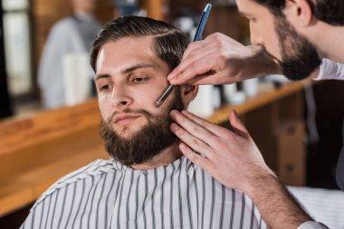 close-up shot of barber shaving man with straight razor