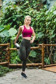 giovane donna atletica che allunga i piedini prima dellallenamento nel parco
