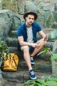 Fotografie atraktivní mladý muž pomocí smartphone, zatímco sedí na kamenné schodiště