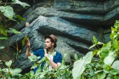 Photo handsome young man in stylish clothes and straw hat hiking in rainforest