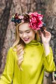 Fotografie junge Frau lächelnd mit Blumenkranz blickte