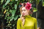 Fotografie attraktive junge Frau mit Blumenkranz mit grünen Regenwald auf Hintergrund