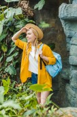 Photo happy young woman in straw hat with backpack hiking in jungle