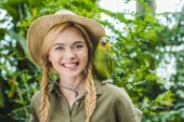 Photo happy young woman in safari suit with parrot on shoulder in jungle