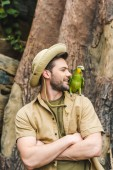 Fotografie handsome young man with parrot on shoulder and crossed arms in jungle