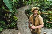 Fotografie hübscher junger Mann mit Papagei auf der Schulter zu Fuß durch den Dschungel park