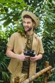 Fotografia giovane sorridente con pappagallo sulla spalla e binocolo nella giungla