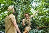 Photo beautiful young couple in safari suits walking by rainforest together