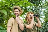 Fotografia giovani coppie felici con pappagallo che si siede sulla spalla delluomo escursionismo insieme nella giungla
