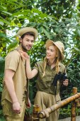 Fotografie attractive young couple in safari suits with binoculars hiking together in rainforest