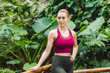 attractive young woman in sportswear leaning back on fence in park