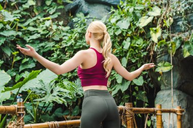 rear view of young woman in sportswear meditating in park