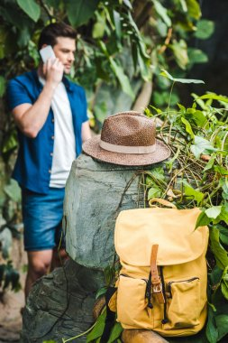 Handsome young man talking by phone in rainforest with backpack and straw hat on foreground stock vector