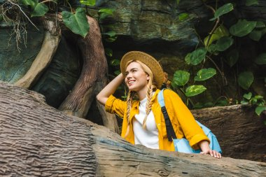 bottom view of smiling young woman in straw hat walking by forest