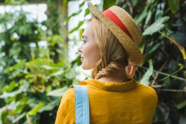 rear view of beautiful young woman in straw hat surrounded with tropical plants