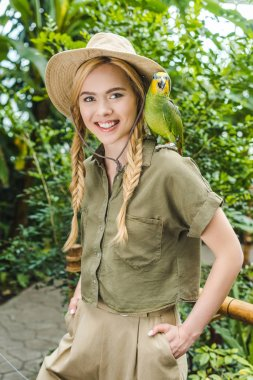 smiling young woman in safari suit with parrot on shoulder in jungle park