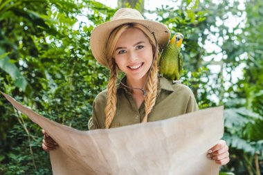 attractive young woman in safari suit with parrot on shoulder navigating in jungle with map