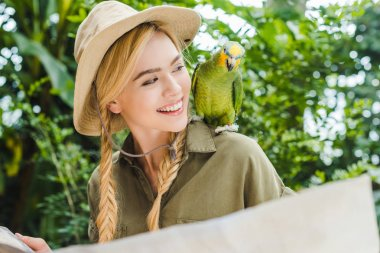 smiling young woman in safari suit looking at parrot on shoulder while navigating in jungle with map