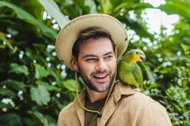 Handsome young man with parrot on shoulder stock vector