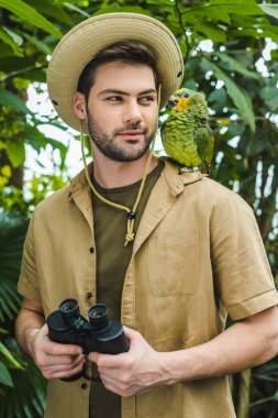 Handsome young man in safari suit looking at parrot on shoulder in jungle stock vector
