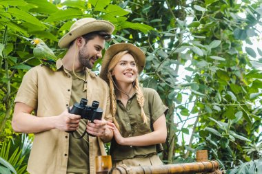 Happy young couple in safari suits with parrot in rainforest stock vector
