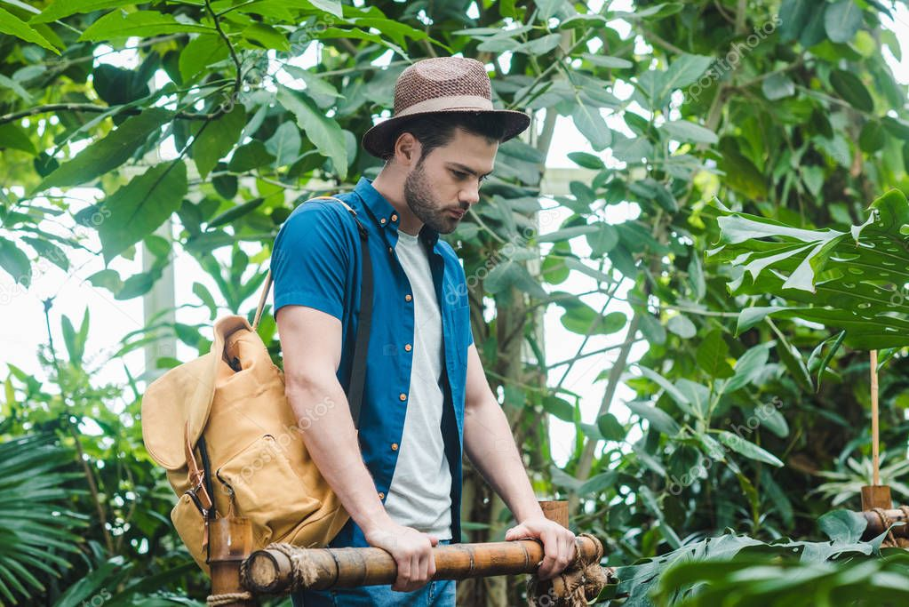 thoughtful young man in stylish clothes with backpack in park with lot of tropical plants