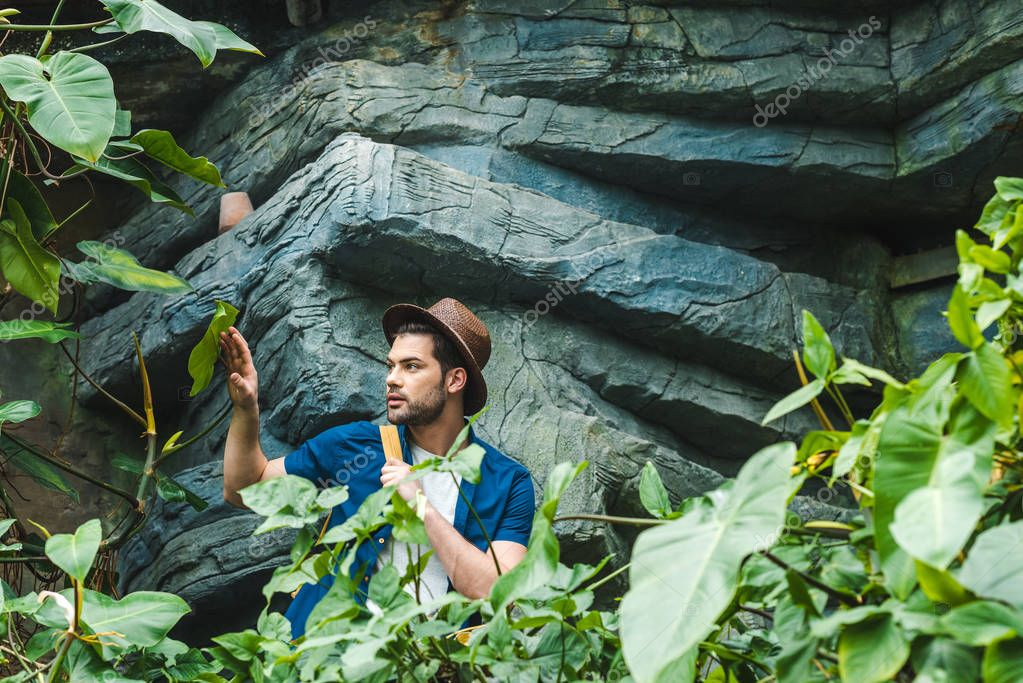 handsome young man in stylish clothes and straw hat hiking in rainforest