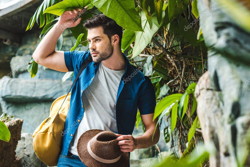 handsome young man in stylish clothes with straw hat in rainforest