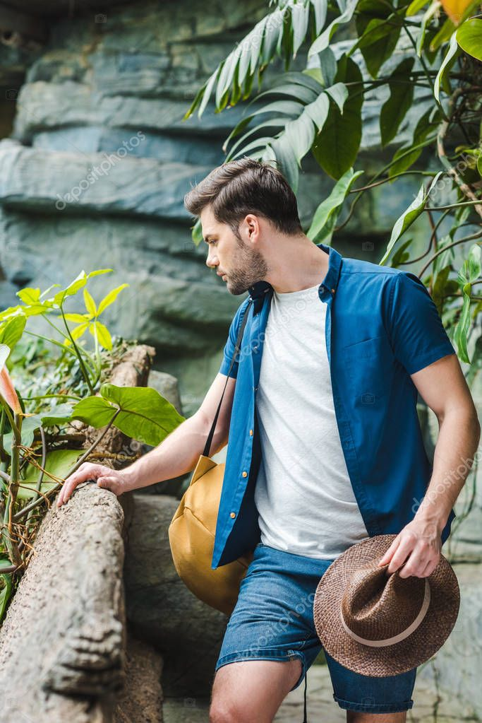 attractive young man in stylish clothes with straw hat in rainforest