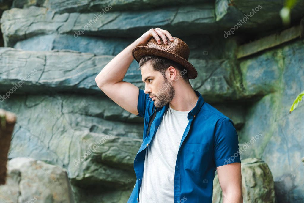 handsome young man in stylish clothes in front of rock in rainforest