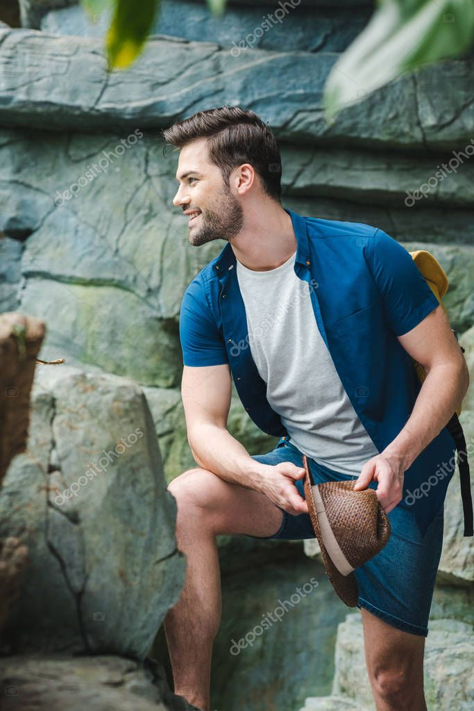 smiling young man in stylish clothes in front of rock in rainforest