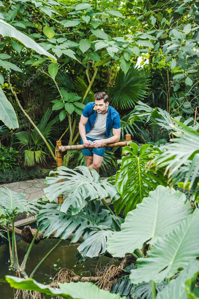 handsome young man in stylish clothing  in park full of exotic plants