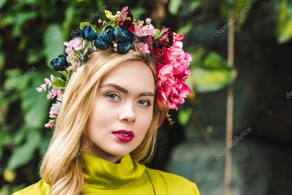 Close-up portrait of beautiful young woman with floral wreath looking at camera stock vector