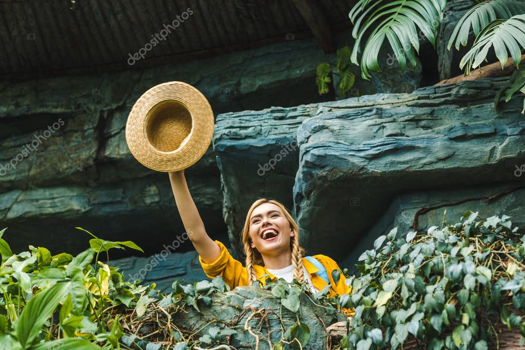bottom view of happy young woman waving with straw hat in jungle