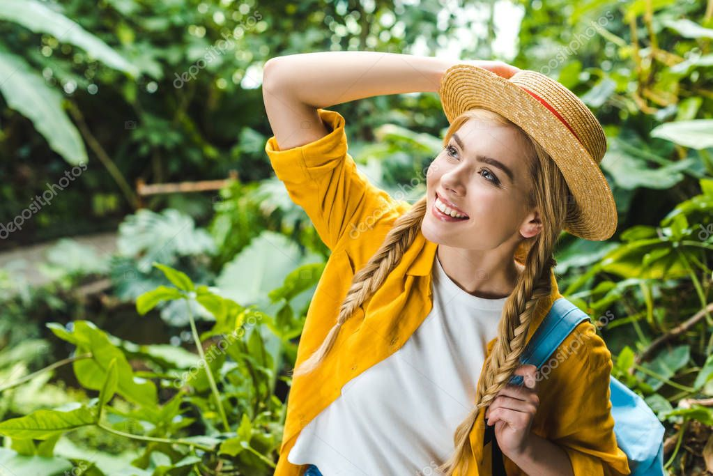 happy young woman in straw hat looking up in forest