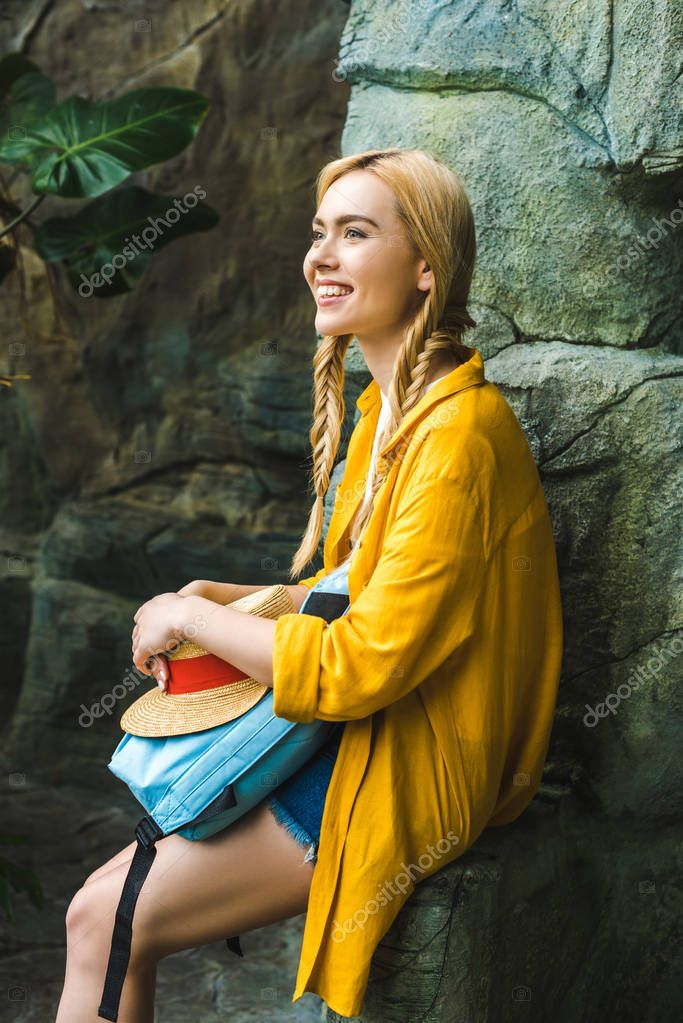 smiling young woman in straw hat relaxing on rocks outdoors